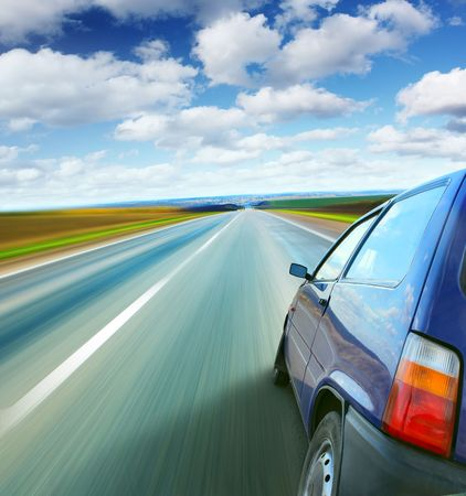 road surface: Liitle car on a blurry road under blue sky Stock Photo