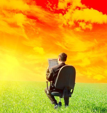 assis par terre: Homme au pr�sident lisant journal sur le pr� vert sous orange sunset Banque d'images