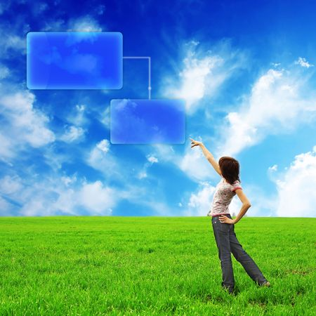 Young woman standing in field with green grass and abstract windows Stock Photo