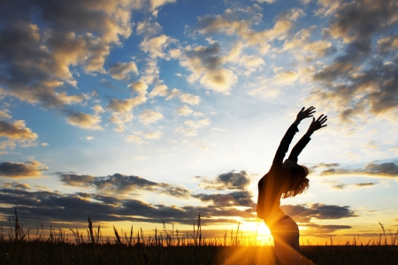 Young women doing exercises on field with grass under sunset light Stock Photo - 5777558