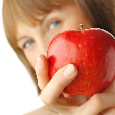 furtive: Young woman with enigmatic glance holding red apple