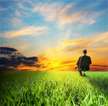 Man on chair in field with dramatic sunset photo