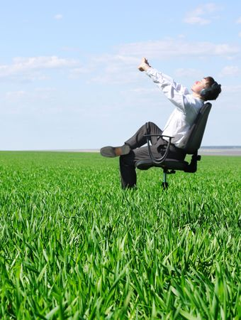 Stretching man on chair in green field Stock Photo - 5802739