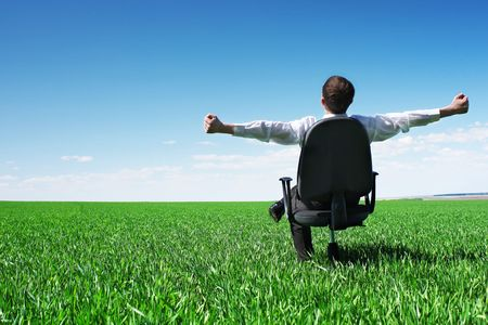 Young businessman sitting on chair in green field photo