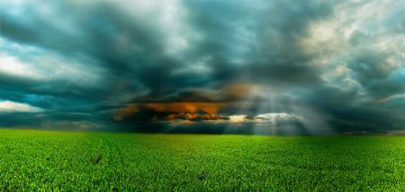 Storm over green field photo