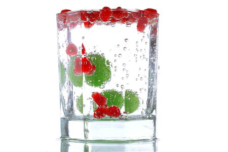 Pomegranate slices and grape in glass with mineral water photo