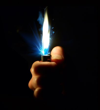 Lighter in hand isolated on black photo
