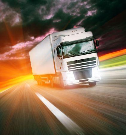 Truck on asphalt road under sunset light photo