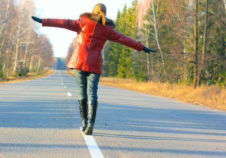 Young woman walking on asphalt road photo