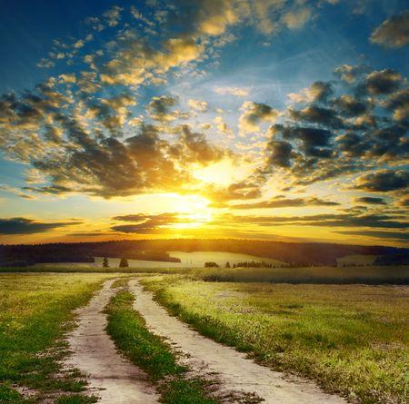 lejos: Road en el campo de la puesta de sol