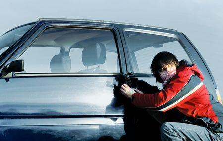 car theft: Chico joven frenado la puerta de un autom�vil y mirando hacia atr�s