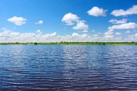 Blue river with ripples and sky with clouds photo