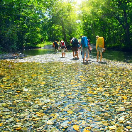 backpackers: Group of backpacers fording cold river