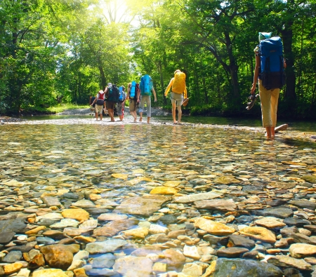 Group of backpacers fording cold river
