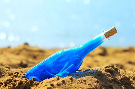 message bottle: Blue bottle in sand