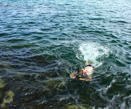 Young woman swimming in sea with mask photo