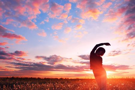 inclination: Young woman on field over sunset Stock Photo