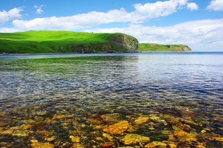 Blue clear sea and hills with green grass photo