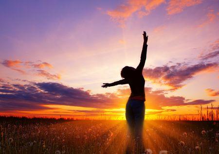 mujer meditando: Silueta de mujer joven sobre Rosa luz sunset  Foto de archivo