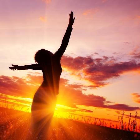 Jonge vrouw silhouet in roze zons ondergang licht