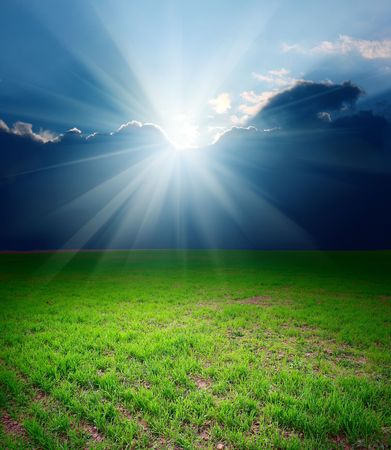 Storm clouds with sun over meadow with green grass Stock Photo