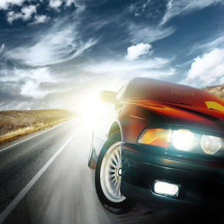 speed line: Sport car on asphalt road under fluffy clouds Stock Photo