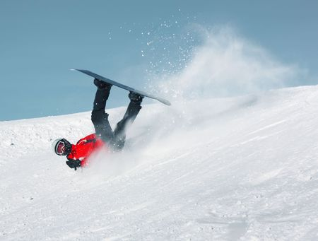 Falling snowboard rider in red suit photo