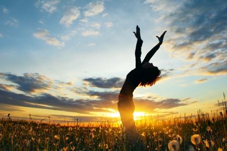 Jonge vrouw op een veld onder zons ondergang licht  Stockfoto