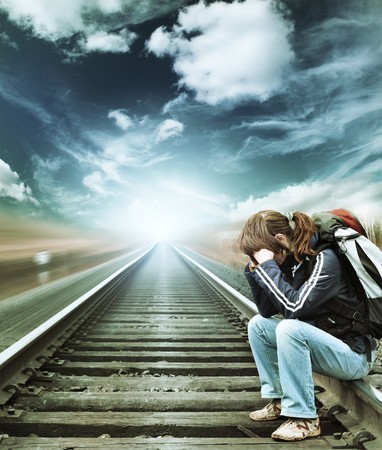 blurr: Alone woman sitting on railroad under blue sky
