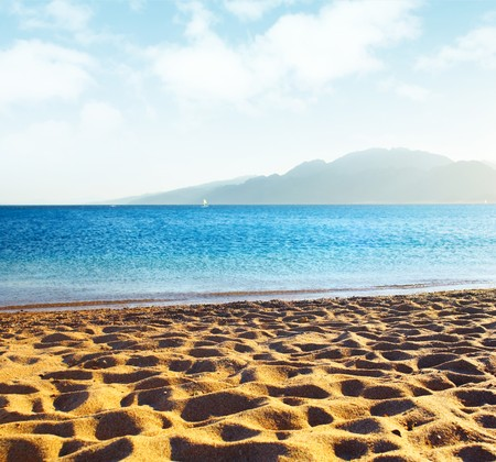 airy: Sand on beach blue sky with airy clouds and sea Stock Photo