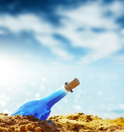 message in bottle: Blue glass bottle in sand and airy clouds like genie