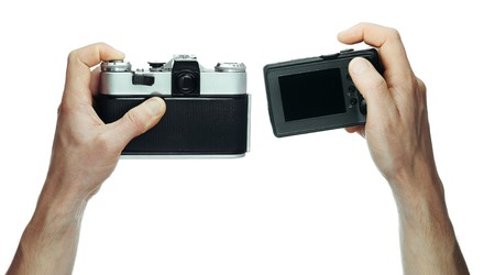 Two cameras - retro and modern in hands photo