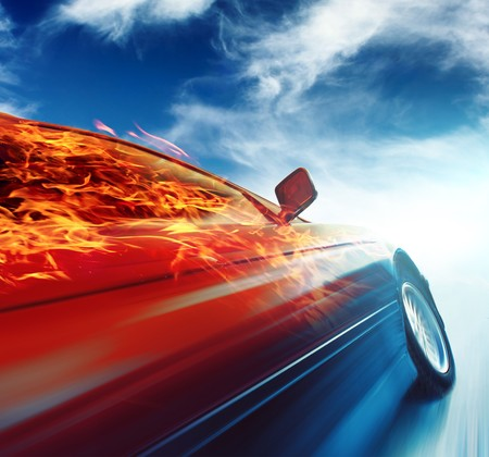 Burning car in motion over blue sky background photo