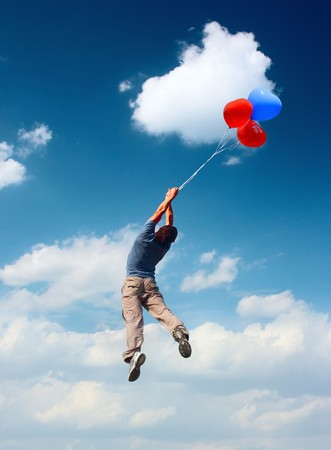 wind force: Man with balloons fliyng in blue cloudy sky