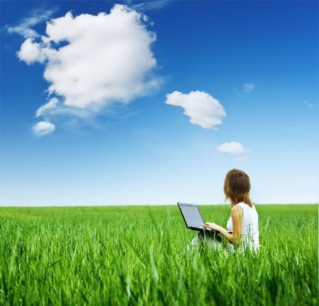 Mujer joven con portátil sentado sobre césped verde  Foto de archivo - 7112202