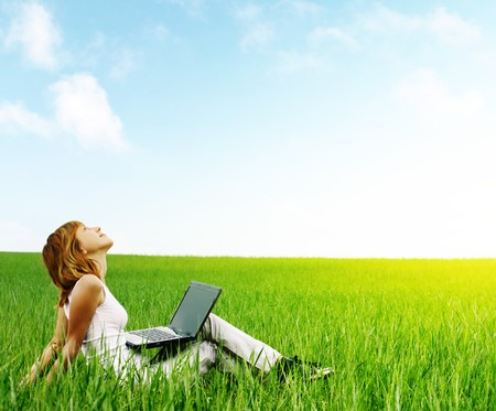 Young smiling woman with laptop sitting in meadow with green grass photo