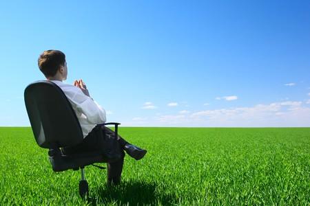 明確な青空に緑の牧草地で椅子に座っている若い男 写真素材