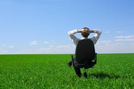 Jonge man zit op een stoel op de weide met groene gras