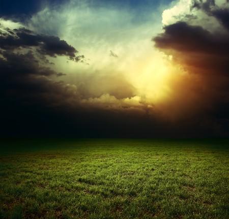 horizonte: Tormenta de nubes oscuras sobre campo con hierba  Foto de archivo