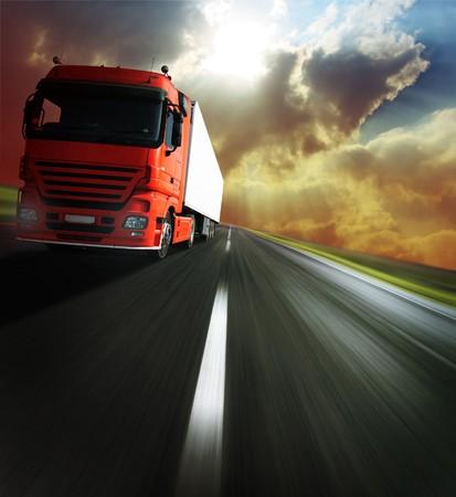 ciężarówka: Ciężki ciężarówka na rozmyty asfaltu drogowego pod Å›wiatÅ'o sÅ'oneczne  Zdjęcie Seryjne