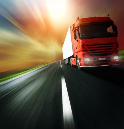 camión: Cami�n rojo en la carretera de asfalto borrosa sobre fondo de cielo nublado
