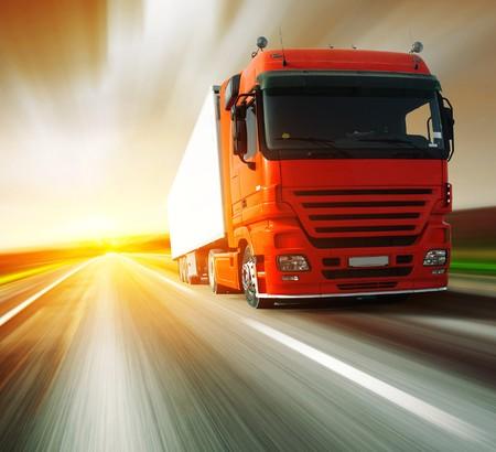 transporte de mercancia: Cami�n rojo en carretera borrosa con cielo borroso