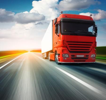 camion: Cami�n rojo en la carretera de asfalto borrosa sobre fondo azul cielo nublado
