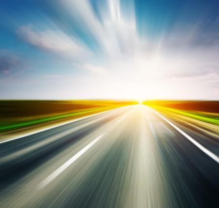 carretera: Carretera borrosa de asfalto vac�a con cielo nublado y la luz del sol