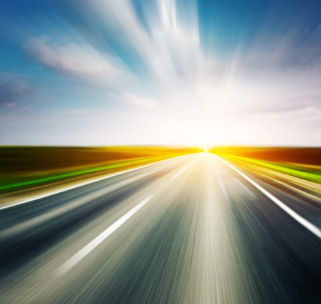 middle of the road: Empty asphalt blurry road with cloudy sky and sunlight Stock Photo