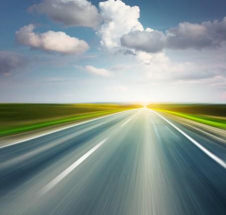 autopista: Carretera de asfalto vac�a con cielo nublado y la luz del sol