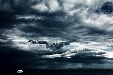 wind storm: Alone white little boat on sea and dark storm clouds Stock Photo