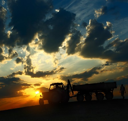 Tractor with cart over cloudy sunset background photo