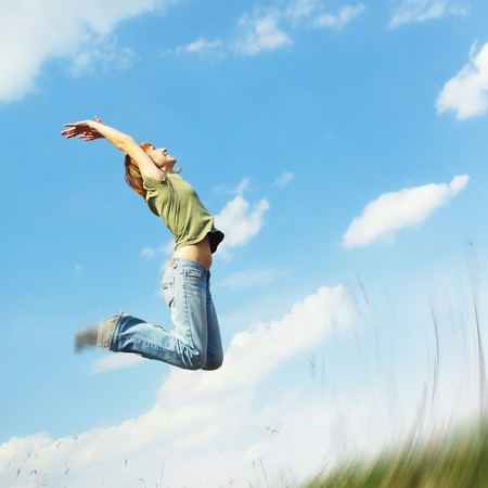 Jumping young woman over blue sky background