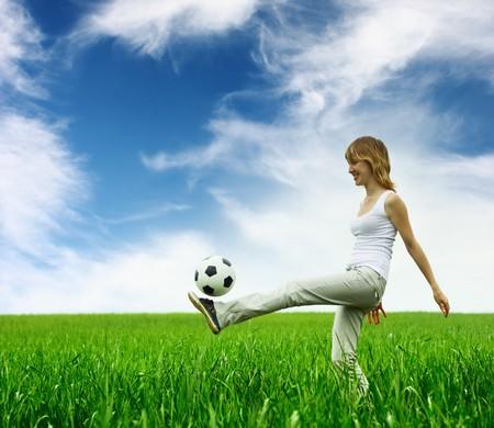 Mujer joven jugando con la pelota en el Prado verde